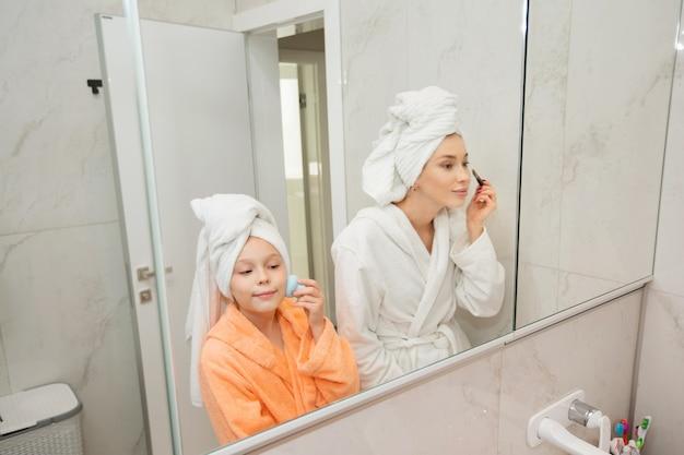 鏡の近くのバスルームでバスローブを着た娘と美しいお母さん