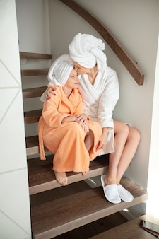 自宅の階段に座っているバスローブを着た娘と美しいお母さん