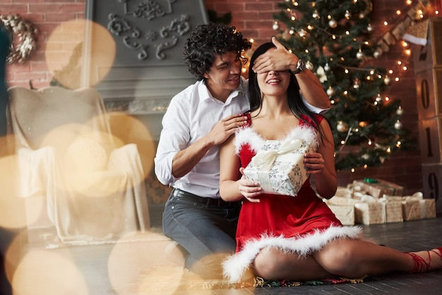 Beautiful moment. man making surprise for his girlfriend. gives new year present. young couple sits on the floor of room of holiday decorated room