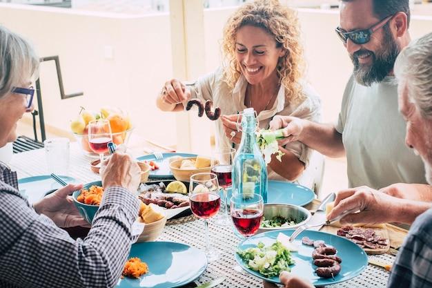 家庭での家族のライフスタイルの美しい瞬間テーブルの上で家で食べ物や飲み物を食べたり飲んだりする-サングラスをかけた男が野菜を食べる-屋外の食べ物とサラダでいっぱいのテーブル