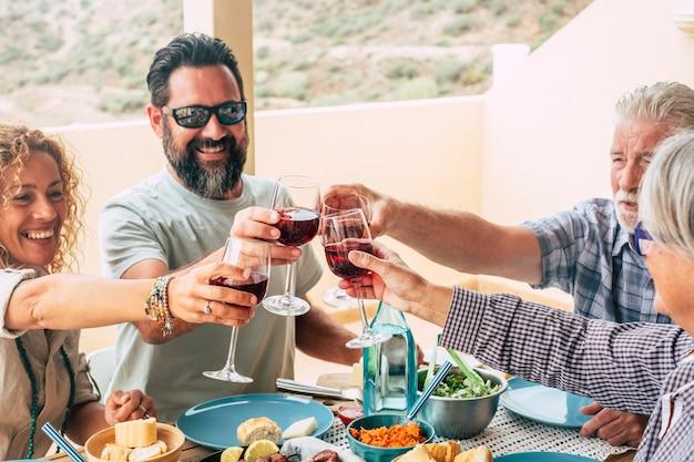 家庭での家族のライフスタイルの美しい瞬間テーブルの上で家で食べ物や飲み物を食べたり飲んだりする-サングラスをかけた男が野菜を食べる-屋外で食べ物やサラダがいっぱいのテーブル