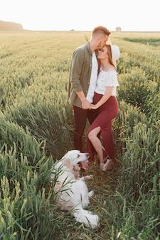 그들의 강아지와 함께 자연 속에서 임신한 부부를 위한 아름다운 행복의 순간. 가족과 임신. 사랑과 부드러움. 행복과 평온. 새로운 삶을 돌봅니다. 자연과 건강.