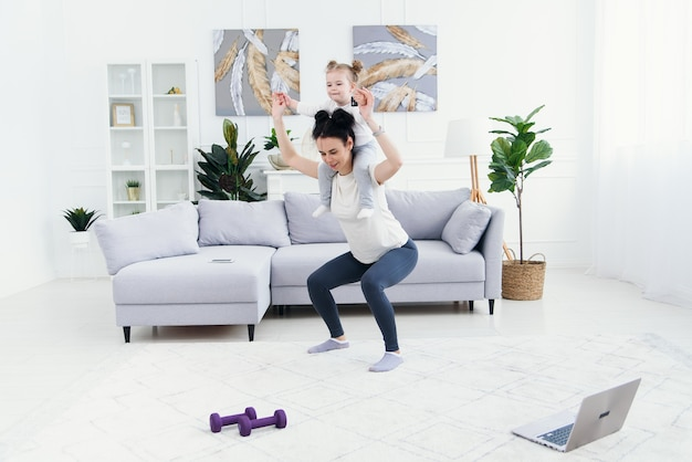 Beautiful mommy and charming little daughter are smiling while doing fitness exercises together at home.