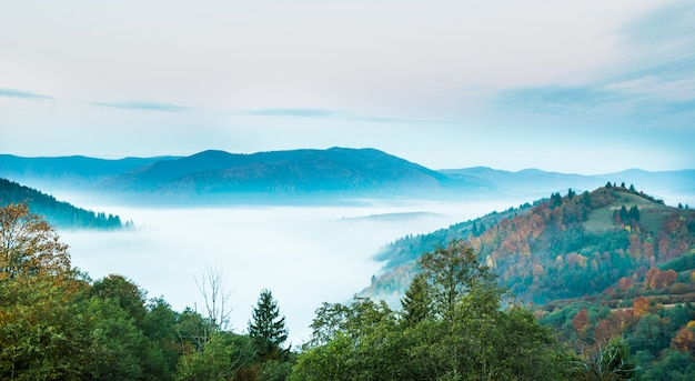 Beautiful morning landscape with autumn foggy mountains.