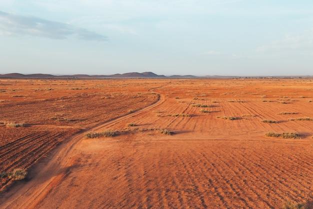 Красивый утренний пейзаж со следом от автомобильных шин в пустыне в марокко.