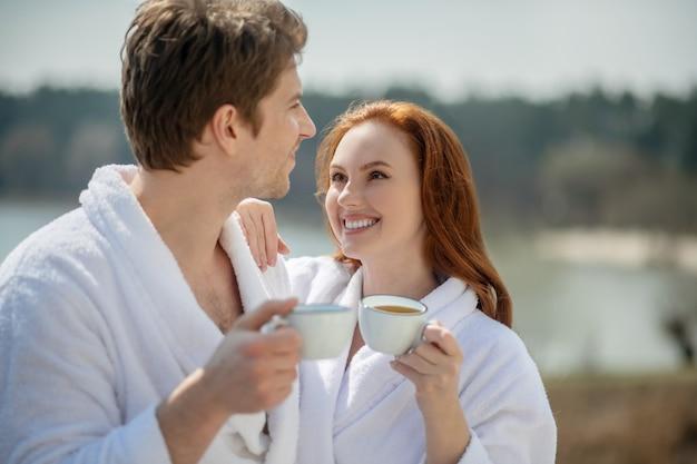 美しい朝。外で朝のコーヒーを持っている幸せな男と女の笑顔