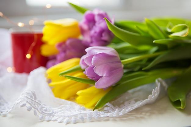 Прекрасное утро, две чашки кофе и букет ярких и красивых тюльпанов.