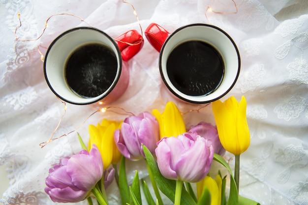 Прекрасное утро, две чашки кофе и букет ярких тюльпанов.