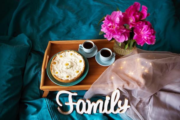 美しい朝のバニラのチーズケーキ、コーヒー、青いカップ、ガラスの花瓶にピンクの牡丹。上からの眺め。