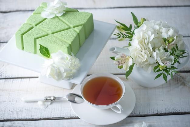 棚の上の正方形の緑のケーキと白いアジサイの美しい朝のウェディングティーテーブル。