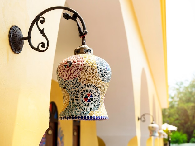 Beautiful moroccan style light lamp, hanging lantern on the outdoor building wall.