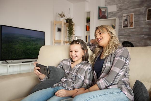 아름다운 엄마와 아이가 거실 소파에서 시간을 보내는 동안 전화 화면을 보고 있습니다.