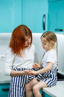 美しい母と娘が台所に座って、抱き合って喜んで笑っています。家族、子供、母性、料理のコンセプト。幸せな家族関係