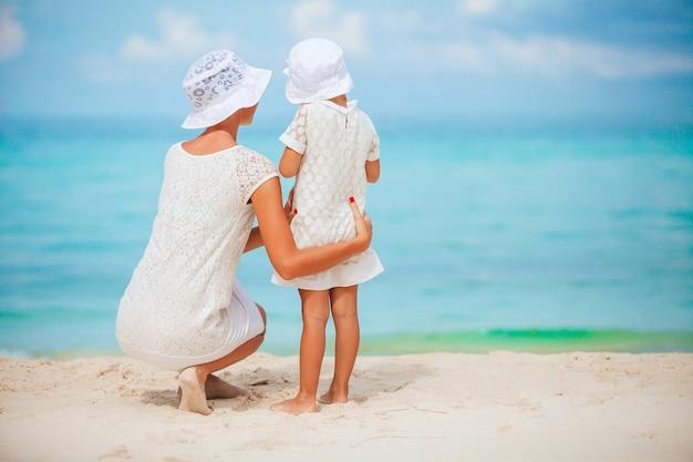 夏休みを楽しんでいるビーチで美しい母と娘