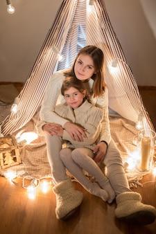 美しい母と娘、クリスマスイブ、居心地の良いインテリアに座っています。新年。