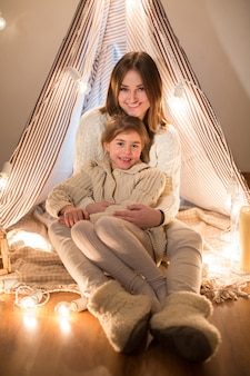 Красивая мать и дочь в канун рождества, сидя в уютном интерьере