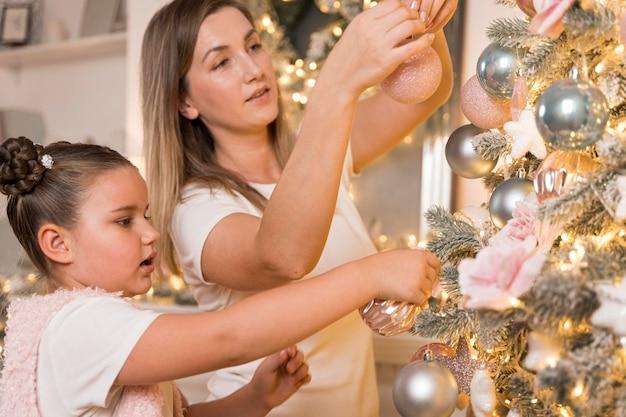 クリスマスツリーを飾る美しい母と娘