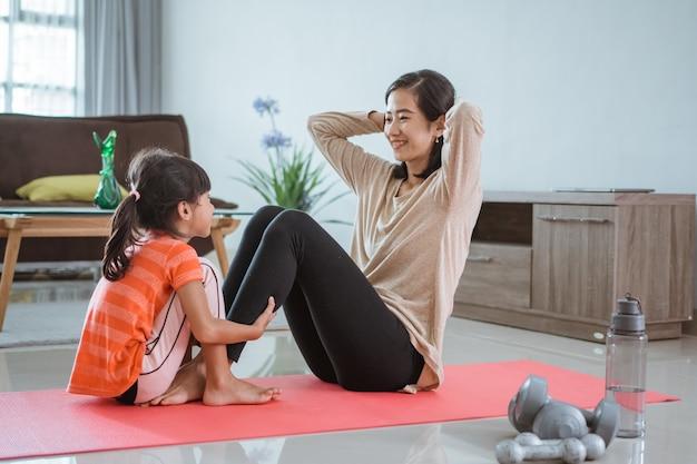 Красивая мать и дочь делают спортивные упражнения дома со своей дочерью вместе