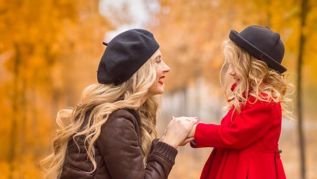 秋の庭で美しい母と娘が優しくお互いを受け入れる