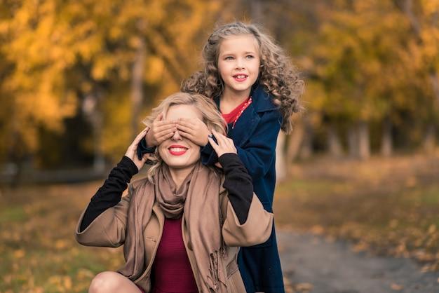 カラフルな秋の屋外で美しい母と娘