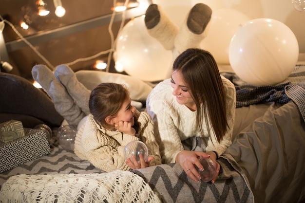 家の居心地の良いインテリアでクリスマスイブにベッドに横たわっている美しい母と娘。新年。