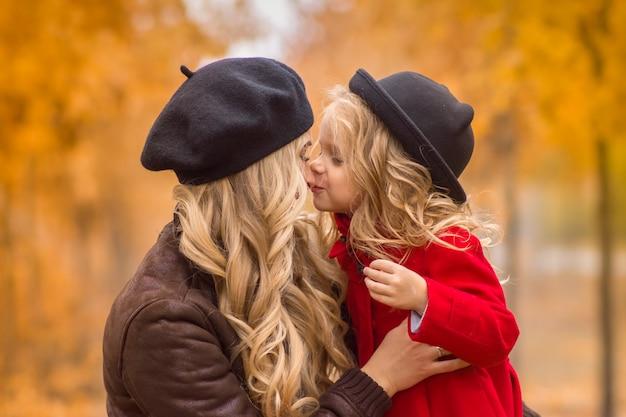 秋の庭の背景に美しい母と娘が優しくお互いを受け入れる