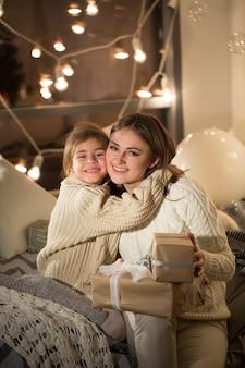 家の居心地の良いインテリアで魔法のクリスマスプレゼントを開く美しい母と娘。新年。