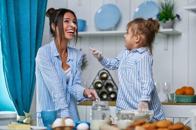 美しい母と娘が小麦粉で台所で遊ぶ。少女は鼻を汚して笑った。