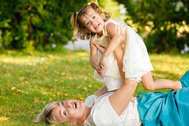 美しい母と娘が公園の芝生の上に横たわって遊ぶ