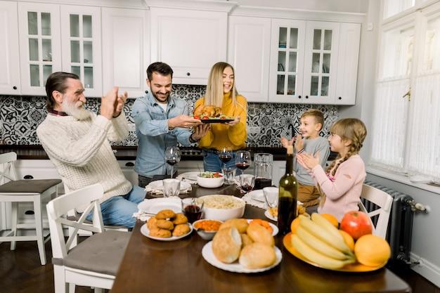 추수 감사절 저녁 식사에 가족을 위해 터키를 들고 아름다운 어머니와 잘 생긴 아버지. 오래 된 할아버지와 아 이들이 테이블에 앉아