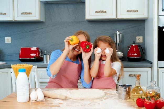 美しい母親と愛らしい娘が料理をしながらキッチンで楽しんで