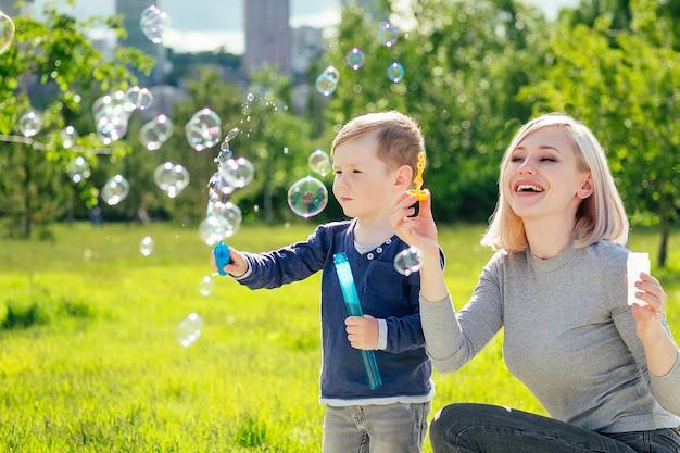 緑の草や木々を背景に公園でシャボン玉を吹く美しい母親と彼女のかわいい赤ちゃんの息子。