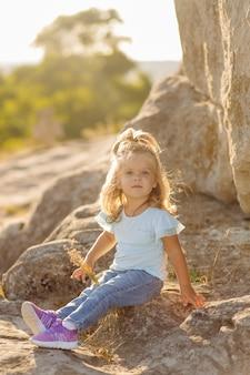 美しい母と彼女のかわいい長い髪の娘は石の牧草地を歩いています