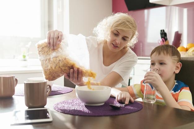 아름다운 어머니와 그녀의 귀여운 아들이 아침에 건강한 콘플레이크를 먹고