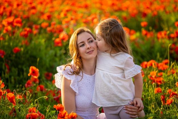 春のケシの花畑、チェコ共和国で美しい母と娘