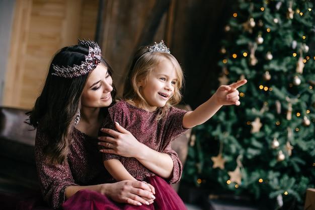ロフトに長い電車があるマルサラ色のドレスを着た女王と王女をイメージした美しい母と娘