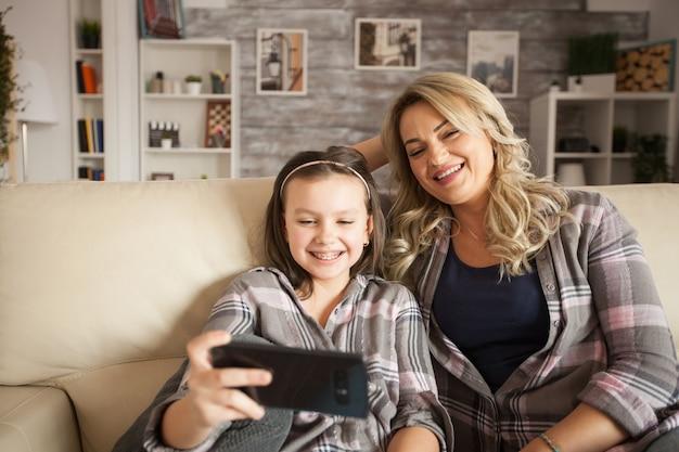 スマートフォンで面白いものを見ている中かっこで美しい母と娘。