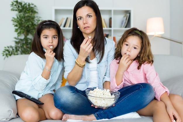 Красивая мать и ее дочери едят попкорн дома.