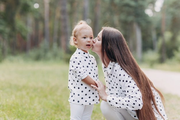 美しい母と彼女の小さな娘の屋外。自然。美容ママと彼女の子供が一緒に公園で遊んでいます。幸せな家族にキスと抱擁。幸せな母の日喜び。ママと赤ちゃん。