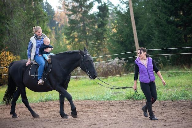 Красивая мать и маленький мальчик, езда на черном коне, испытывают счастливые веселые эмоции