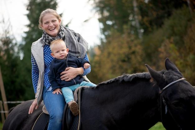 아름다운 어머니와 검은 말을 타고 작은 아기 아들은 행복한 재미있는 감정을 가지고