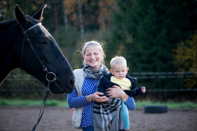 Красивая мать и маленький мальчик-сын с черной лошадью на открытом воздухе