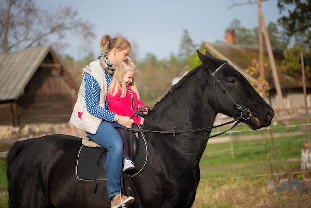 Красивая мать и маленькая девочка дочка верхом на черном коне радуются веселым эмоциям