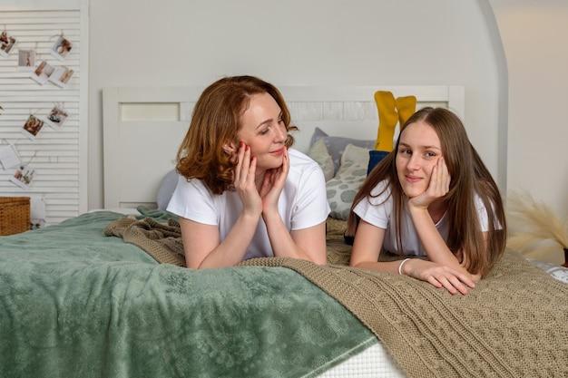 美しい母と10代の娘が笑顔で家でポーズをとる。