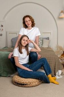 Красивая мать и дочь-подросток улыбаются и позируют дома.