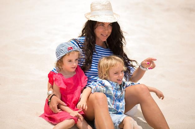 아름다운 어머니와 해변 휴가를 즐기는 두 아이