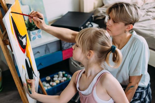 Красивая мама-художник и ее ребенок раскрашивают дома картину акриловыми красками