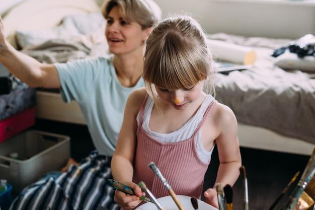 美しい母の芸術家と彼女の子供はアクリル絵の具で家で絵を描く