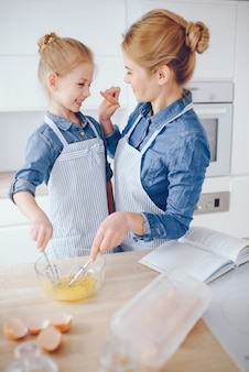 Beautiful mother in a blue shirt and apron is preparing dinner at home in the kitchen