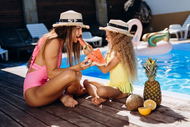 Beautiful mother and cute daughter having fun by the pool